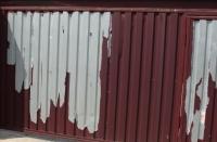 Облезшее покрытие на заборе из профнастила