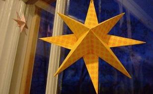 Объемная звезда из бумаги украшает окно к Новому году