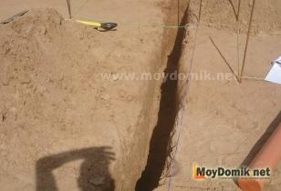 Рытье траншеи для укладки канализационной трубы под уклоном