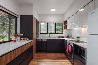 Дизайн кухни с двумя окнами, объединенными одной столешницей