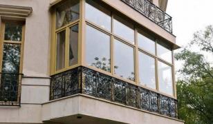 На фото французское остекление балкона с кованым ограждением по периметру