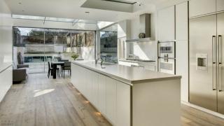 Дизайн просторной кухни-гостиной с панорамным остеклением и террасой